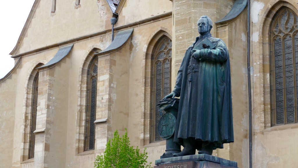 Statuia Teutsch and behind the Protestant Lutheran Church (Biserica Parohiala Evanghelica)